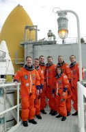 KENNEDY SPACE CENTER, FLA. -- After emergency exit practice on Launch Pad 39A, the STS-109 crew poses for a photo on the 225-foot level of the Fixed Service Structure. Clockwise from left are Mission Specialist John Grunsfeld; Pilot Duane Carey; Mission Specialist Richard Linnehan; Commander Scott Altman; and Mission Specialists Michael Massimino, James Newman and Nancy Currie. Behind them at left can be seen one of the twin solid rocket boosters and the larger external tank that will propel Columbia and the crew into space. The goal of mission STS-109, a Hubble Servicing Mission, is to replace Solar Array 2 with Solar Array 3, replace the Power Control Unit, remove the Faint Object Camera and install the ACS, install the Near Infrared Camera and Multi-Object Spectrometer (NICMOS) Cooling System, and install New Outer Blanket Layer insulation. The launch will be the first for Columbia after returning from California where it underwent extensive maintenance, inspections and enhancements. More than 100 upgrades make Columbia safer and more reliable than ever before. Columbia is scheduled to be launched Feb. 28