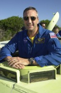 KENNEDY SPACE CENTER, FLA. - STS-109 Mission Specialist Michael Massimino is ready to practice driving the M-113 armored personnel carrier, part of emergency egress training at the launch pad. Behind him is Commander Scott Altmann. Crew members are taking part in Terminal Countdown Demonstration Test activities, which also include a simulated launch countdown. STS-109 is a Hubble Space Telescope Servicing Mission, with goals to replace Solar Array 2 with Solar Array 3, replace the Power Control Unit, remove the Faint Object Camera and install the Advanced Camera for Surveys (ACS), install the Near Infrared Camera and Multi-Object Spectrometer (NICMOS) Cooling System, and install New Outer Blanket Layer insulation. The 11-day mission will require grasping the satellite with a robotic arm in order for the crew to perform the tasks during five spacewalks. Launch of STS-109 aboard Space Shuttle Columbia is scheduled for Feb. 28, 2002