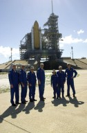 KENNEDY SPACE CENTER, FLA. -- The STS-109 crew poses for a photo at Launch Pad 39A during a break in training. From left are Mission Specialists Michael Massimino and Richard Linnehan, Pilot Duane Carey, Commander Scott Altman, and Mission Specialists Nancy Currie, John Grunsfeld and James Newman. Grunsfeld is also Payload Commander on the mission. The crew is taking part in Terminal Countdown Demonstration Test activities that include emergency egress training and a simulated countdown at the pad. Columbia is scheduled to be launched Feb. 28 on mission STS-109, a Hubble Servicing Mission. The goal of the mission is to replace Solar Array 2 with Solar Array 3, replace the Power Control Unit, remove the Faint Object Camera and install the ACS, install the Near Infrared Camera and Multi-Object Spectrometer (NICMOS) Cooling System, and install New Outer Blanket Layer insulation. In the background can be seen the external tank flanked by the twin solid rocket boosters that will propel Columbia (unseen on the other side of the stack) into space. The launch will be the first for Columbia after returning from California where it underwent extensive maintenance, inspections and enhancements. More than 100 upgrades make Columbia safer and more reliable than ever before