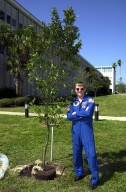 KENNEDY SPACE CENTER, FLA. -- Astronaut Frank Culbertson stands next to the cherry laurel tree he has dedicated and helped plant near KSC Headquarters Building. The tree commemorates his stay on and safe return from the International Space Station as a member of the Expedition 3 crew. Culbertson served as commander for the four-month stay, August to December 2001. The tree planting is a tradition for the Expedition crews.