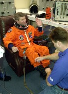 """KENNEDY SPACE CENTER, FLA. -- STS-110 Pilot Stephen N. Frick waves while a suit technician makes final adjustments on his launch and entry suit for the launch scheduled for 4:40 p.m. EDT. Frick is making his first Shuttle flight. STS-110 is the 13th assembly flight to the International Space Station, carrying the S0 Integrated Truss Structure and Mobile Transporter (MT). On the 11-day mission, the mission features four spacewalks to attach the S0 truss, which will become the backbone of the Space Station, to the U.S. Lab, """"Destiny."""" The MT, a space """"railcar,"""" is attached to the truss segment and will make its debut run during the flight"""