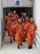 """KENNEDY SPACE CENTER, FLA. - Showing their eagerness for launch, the STS-110 crew wave as they stride out of the Operations and Checkout Building. Leading the way in the front row are Pilot Stephen N. Frick (left) and Commander Michael J. Bloomfield (right); in the second row are Mission Specialists Rex J. Walheim and Ellen Ochoa; third row, Jerry L. Ross and Lee M.E. Morin; in the rear is Mission Specialist Steven L. Smith. STS-110 is the 13th assembly flight to the International Space Station, carrying the S0 Integrated Truss Structure and Mobile Transporter (MT). On the 11-day mission, the mission features four spacewalks to attach the S0 truss, which will become the backbone of the Space Station, to the U.S. Lab, """"Destiny."""" The MT, a space """"railcar,"""" is attached to the truss segment and will make its debut run during the flight. Launch is scheduled for 4:40 p.m. EDT (20:40 GMT). Photo by Scott Andrews"""