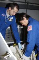 """KENNEDY SPACE CENTER, FLA. -- In the Orbiter Processing Facility, STS-111 Mission Specialists Phillippe Perrin (left) and Franklin Chang-Diaz (right) check equipment for their mission. Perrin is with the French Space Agency (CNES). Perrin and Chang-Diaz, with other crew members, are taking part in a Crew Equipment Interface Test in preparation for launch. Mission STS-111 will carry to the International Space Station the Multipurpose Logistics Module (MPLM), filled with experiment racks and three stowage and resupply racks, and the Mobile Base System (MBS), which will attach to the Mobile Transporter and complete the Canadian Mobile Servicing System, or MSS. The Station's mechanical arm will then have the capability to """"inchworm"""" from the U.S. Lab to the MSS and travel along the truss to work sites on the Station. Launch of Endeavour on mission STS-111 is scheduled for May 30, 2002"""