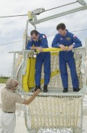 """KENNEDY SPACE CENTER, FLA. -- During emergency egress training on the Launch Pad 39A, STS-111 Mission Specialist Philippe Perrin, with the French Space Agency, and Expedition 5 crew member Sergei Treschev, with the Russian Space Agency, get directions about using the slidewire basket they are standing in. The training for the two crews is part of Terminal Countdown Demonstration Test activities, which also include a simulated launch countdown. Mission STS-111 is known as Utilization Flight 2, carrying supplies and equipment in the Multi-Purpose Logistics Module Leonardo to the International Space Station. The payload also includes the Mobile Base System, which will be installed on the Mobile Transporter to complete the Canadian Mobile Servicing System, or MSS, and a replacement wrist/roll joint for Canadarm 2. The mechanical arm will then have the capability to """"inchworm"""" from the U.S. Lab Destiny to the MSS and travel along the truss to work sites. Expedition 5 will travel to the Station on Endeavour as the replacement crew for Expedition 4, who will return to Earth aboard the orbiter. Launch is scheduled for May 30, 2002"""