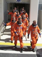 """KENNEDY SPACE CENTER, FLA. - The STS-111 and Expedition 5 crews eagerly stride from the Operations and Checkout Building toward the waiting Astrovan that will take them to Launch Pad 39A and Space Shuttle Endeavour. From front to back are Pilot Paul Lockhart and Commander Kenneth Cockrell; astronaut Peggy Whitson and Expedition 5 Commander Valeri Korzun (RSA); cosmonaut Sergei Treschev (RSA); and Mission Specialists Philippe Perrin (CNES) and Franklin Chang-Diaz. STS-111 is the second Utilization Flight to the International Space Station, carrying the Multi-Purpose Logistics Module Leonardo, the Mobile Base System (MBS), and a replacement wrist/roll joint for the Canadarm 2. Also onboard Space Shuttle Endeavour is the Expedition 5 crew who will replace Expedition 4 on board the Station. The MBS will be installed on the Mobile Transporter to complete the Canadian Mobile Servicing System, or MSS. The mechanical arm will then have the capability to """"inchworm"""" from the U.S. Lab Destiny to the MSS and travel along the truss to work sites. Expedition 4 crew members will return to Earth with the STS-111 crew on Endeavour."""