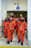 """KENNEDY SPACE CENTER, FLA. -- The STS-107 crew, waving to onlookers, exits the Operations and Checkout Building on their way to Launch Pad 39A for liftoff. Leading the way are Pilot William """"Willie"""" McCool (left) and Commander Rick Husband (right). Following in the second row are Mission Specialists Kalpana Chawla (left) and Laurel Clark; in the rear are Payload Specialist Ilan Ramon, Payload Commander Michael Anderson and Mission Specialist David Brown. Ramon is the first astronaut from Israel to fly on a Shuttle. The 16-day mission is devoted to research and will include more than 80 experiments that will study Earth and space science, advanced technology development, and astronaut health and safety. The payload on Space Shuttle Columbia includes FREESTAR (Fast Reaction Experiments Enabling Science, Technology, Applications and Research) and the SHI Research Double Module (SHI/RDM), known as SPACEHAB. Experiments on the module range from material sciences to life sciences. Liftoff is scheduled for 10:39 a.m. EST."""