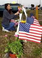 KENNEDY SPACE CENTER, FLA. - At the corner of Contractors Road and the Saturn Causeway, a KSC employee places an STS-107 crew photograph and surrounds it with flowers and U.S. flags as a memorial tribute to the fallen crew of Columbia. The Space Shuttle Columbia and her crew of seven were lost on Feb. 1, 2003, over East Texas as they returned to Earth after a 16-day research mission, STS-107.