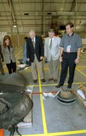 """KENNEDY SPACE CENTER, FLA. - In the RLV Hangar, (from left) Lisa Malone, acting deputy director of External Relations & Business Development at KSC, former astronauts Jim Lovell and Wally Schirra, and Steve Altemus, Space Shuttle test director, look over pieces of Columbia debris. Lovell and Schirra visited several sites around the Center, encouraging workers to help get the space program """"back on its feet."""" The RLV Hangar is where Columbia debris is being collected and examined as part of the investigation into the tragedy that claimed the orbiter and lives of seven astronauts returning from mission STS-107."""