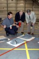 """KENNEDY SPACE CENTER, FLA. - In the RLV Hangar, Space Shuttle Test Director Steve Altemus (left) shows former astronauts Jim Lovell (center) and Wally Schirra (right) a piece of debris from Columbia. The latter two visited several sites around the Center, encouraging workers to help get the space program """"back on its feet."""" The RLV Hangar is where Columbia debris is being collected and examined as part of the investigation into the tragedy that claimed the orbiter and lives of seven astronauts returning from mission STS-107."""