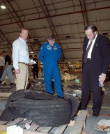 KENNEDY SPACE CENTER, FLA. - In the RLV Hangar at KSC, Shuttle Launch Director Mike Leinbach (left), former payload specialist Dr. Roger Crouch (center) and NASA Chief of Staff and White House liaison Courtney Stadd look at one of Space Shuttle Columbia's tires. The debris is one of more than 35,000 pieces collected so far. More than 1,218 pieces have been identified. The search of more than 500,000 acres of primary recovery area for Columbia material has passed the halfway mark. To date about 28 percent of Columbia, by weight, has been delivered to the hangar.