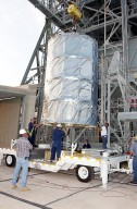 KENNEDY SPACE CENTER, FLA. - On Launch Complex 17-B, Cape Canaveral Air Force Station, the Space Infrared Telescope Facility (SIRTF) observatory is lowered onto a transporter to be taken back to NASA Spacecraft Hangar AE. SIRTF will remain in the clean room at Hangar AE until it returns to the pad in early August.