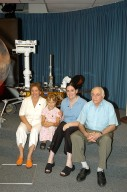 "KENNEDY SPACE CENTER, FLA. - Siberian-born Sofi Collis (second from left), the third grade student winner of the ""Name the Rovers"" contest, poses with her adopted American family. The names she proposed -- Spirit and Opportunity -- were announced today in a press conference held by NASA Administrator Sean O'Keefe. NASA's twin Mars Exploration Rovers are designed to study the history of water on Mars. These robotic geologists are equipped with a robotic arm, a drilling tool, three spectrometers, and four pairs of cameras that allow them to have a human-like, 3D view of the terrain. Each rover could travel as far as 100 meters in one day to act as Mars scientists' eyes and hands, exploring an environment where humans are not yet able to go. MER-A, with the rover Spirit aboard, is scheduled to launch on June 8 at 2:06 p.m. EDT, with two launch opportunities each day during a launch period that closes on June 24."