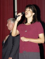 KENNEDY SPACE CENTER, FLA. - Suzy Cunningham sings the national anthem to kick off Center Director Jim Kennedy?s first all-hands meeting conducted for employees. She is senior spaceport manager, NASA/Air Force Spaceport Planning and Customer Service Office. Making presentations were Dr. Woodrow Whitlow Jr., KSC deputy director; Tim Wilson, assistant chief engineer for Shuttle; and Bill Pickavance, vice president and deputy program manager, Florida operations, United Space Alliance. Representatives from the Shuttle program and contractor team were on hand to discuss the Columbia Accident Investigation Board report and where KSC stands in its progress toward return to flight.
