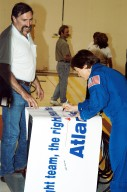 KENNEDY SPACE CENTER, FLA. - STS-114 Mission Specialist Wendy Lawrence autographs the sign presented to workers in the Orbiter Processing Facility. Lawrence is a new addition to the crew. The STS-114 crew is at KSC to take part in crew equipment and orbiter familiarization.