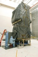 KENNEDY SPACE CENTER, FLA. - In the clean room at NASA?s Hangar AE on Cape Canaveral Air Force Station (CCAFS), Spectrolab technicians begin lifting the protective cover from the Swift spacecraft. Two of Swift?s solar cells on the solar array will be removed and replaced. Swift is a first-of-its-kind, multi-wavelength observatory dedicated to the study of gamma-ray burst (GRB) science. Its three instruments will work together to observe GRBs and afterglows in the gamma-ray, X-ray, ultraviolet and optical wavebands. The main mission objectives for Swift are to determine the origin of gamma-ray bursts, classify gamma-ray bursts and search for new types, determine how the blast wave evolves and interacts with the surroundings, use gamma-ray bursts to study the early universe and perform the first sensitive hard X-ray survey of the sky. Swift is scheduled to launch Oct. 26 from Launch Pad 17-A, CCAFS, on a Boeing Delta 7320 rocket.