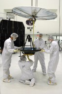 KENNEDY SPACE CENTER, FLA. - Ball Aerospace technicians at Astrotech in Titusville, Fla., attach on overhead crane to the high-gain communications antenna to be installed on the Deep Impact spacecraft. A NASA Discovery mission, Deep Impact will probe beneath the surface of Comet Tempel 1 on July 4, 2005, when the comet is 83 million miles from Earth, and reveal the secrets of its interior. During the encounter phase, the high-gain antenna transmits near-real-time images of the impact back to Earth. The spacecraft is scheduled to launch Jan. 8 aboard a Boeing Delta II rocket from Launch Complex 17-B at Cape Canaveral Air Force Station, Fla.