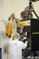 KENNEDY SPACE CENTER, FLA. - At Astrotech Space Operations in Titusville, Fla., a Ball Aerospace technician helps guide the flight battery toward the flyby spacecraft on Deep Impact where it will be installed. About the size of a Ford Explorer, the flyby spacecraft is three-axis stabilized and uses a fixed solar array and a small NiH2 battery for its power system. A NASA Discovery mission, Deep Impact will probe beneath the surface of Comet Tempel 1 on July 4, 2005, when the comet is 83 million miles from Earth. During the encounter phase when the comet collides with the impactor projectile propelled into its path, the spacecraft?s high-gain antenna will transmit near-real-time images of the impact back to Earth. The spacecraft is scheduled to launch Jan. 8 aboard a Boeing Delta II rocket from Launch Complex 17-B at Cape Canaveral Air Force Station, Fla.