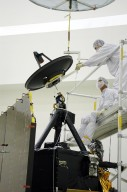 KENNEDY SPACE CENTER, FLA. - Ball Aerospace technicians at Astrotech in Titusville, Fla., guide the high-gain communications antenna toward the attach-point on the Deep Impact spacecraft. A NASA Discovery mission, Deep Impact will probe beneath the surface of Comet Tempel 1 on July 4, 2005, when the comet is 83 million miles from Earth, and reveal the secrets of its interior. During the encounter phase, the high-gain antenna transmits near-real-time images of the impact back to Earth. The spacecraft is scheduled to launch Jan. 8 aboard a Boeing Delta II rocket from Launch Complex 17-B at Cape Canaveral Air Force Station, Fla.