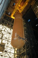 """KENNEDY SPACE CENTER, FLA. - Viewed from the floor of the Vehicle Assembly Building, the redesigned External Tank is seen being lifted to the top where it will be lifted into the """"checkout cell"""" where the tank?s mechanical, electrical and thermal protection systems are inspected. The tank will also undergo new processes resulting from its redesign, including inspection of the bipod heater and External Tank separation camera. The tank will be prepared for """"mating"""" to the Shuttle?s Solid Rocket Boosters. When preparations are complete, the tank will be lifted from the checkout cell, moved across the transfer aisle and into High Bay 1. It will be lowered and attached to the boosters, which are sitting on the Mobile Launch Platform. The SRBs and ET will be flying with Shuttle Discovery for the Return to Flight mission STS-114. The launch planning window is May 12 to June 3, 2005."""
