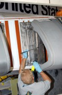 KENNEDY SPACE CENTER, FLA. - In the Orbiter Processing Facility, Mel Romans, with United Space Alliance, prepares the area on orbiter Discovery?s leftwing for installation of the final Reinforced Carbon-Carbon (RCC) panel. The leading edges of each of an orbiter?s wings have 22 RCC panels. They are light gray and made entirely of carbon composite material, which protect the orbiter during re-entry. The molded components are approximately 0.25- to 0.5-inch thick and capable of withstanding temperatures up to 3,220 degrees F. Following the Columbia accident in February 2002, which was caused by a breach in an RCC panel that allowed hot gases into the vehicle, each panel on Discovery was removed and thoroughly inspected before final reinstallation. Discovery is the designated orbiter to fly on the Return to Flight mission STS-114, the first Space Shuttle to launch since the accident. The launch window for the mission is May 12 to June 3, 2005.