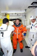 KENNEDY SPACE CENTER, FLA. -With the help of the Closeout Crew in the White Room on Launch Pad 39B, STS-114 Mission Specialist Charles Camarda adjusts his launch suit before entering Space Shuttle Discovery. The crew is taking part in a full dress rehearsal for launch, including countdown and culminating in main engine cutoff. The rehearsal is the final part of Terminal Countdown Demonstration Test (TCDT) activities that the crew has been involved in for three days. TCDT provides the crew of each mission an opportunity to participate in various simulated countdown activities, including equipment familiarization and emergency egress training. STS-114 is the first Return to Flight mission to the International Space Station. The launch window extends July 13 through July 31.