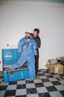 """KENNEDY SPACE CENTER, FLA. - NASA Special Agent Dan Oakland holds up a long-lost spacesuit recently uncovered at the Cape Canaveral Air Force Station (CCAFS) in Florida. A recent venture into a long-locked room at CCAFS uncovered interesting artifacts of a by-gone era: retired space suits from Americans who trained in the 1960s to be astronauts aboard an Air Force orbiting reconnaissance laboratory. Two security officers were doing a check of a facility at Launch Complex 5/6 blockhouse. Oakland and Security Manager Henry Butler, who is with Delaware North Parks and Resorts, the company that oversees the museum, discovered a locked room. Space suits from the Air Force?s planned Manned Orbiting Laboratory (MOL) program were found in the room Begun in 1964, the MOL program was an Air Force initiative that would have sent Air Force astronauts to a space station in a Gemini capsule. After spending a few weeks in orbit, the crew would undock and return to Earth. A test launch from Complex 40 on Nov. 30, 1966, of a MOL was conducted with an unmanned Gemini capsule. The MOL was constructed from tankage of a Titan II rocket. The operational MOL was planned to be launched into a polar orbit from Vandenberg Air Force Base in California. The Air Force abandoned the program in 1969, but the program produced a great deal of technological development, and three groups of military officers trained to be MOL astronauts. When the program was cancelled, seven of the younger astronauts were transferred to the agency?s human space flight program and went on to have standout careers. Among them were Robert Crippen, pilot of the first Space Shuttle mission, and Richard H. """"Dick"""" Truly, who later became NASA Administrator."""