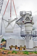 KENNEDY SPACE CENTER, FLA. - At a radar site on North Merritt Island, Fla., one of two counterweights is being lifted for installation on a support structure (right) for a 50-foot C-band radar antenna dish. The radar will be used for Shuttle missions to track the launches and observe possible debris coming from the Shuttle. It will be used for the first time on STS-114. The launch window for the first Return to Flight mission is July 13 to July 31.