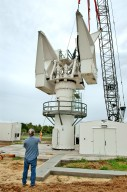 KENNEDY SPACE CENTER, FLA. - At a radar site on North Merritt Island, Fla., the second counterweight (right side) is lifted into place on the support structure for a 50-foot C-band radar antenna dish. The radar will be used for Shuttle missions to track the launches and observe possible debris coming from the Shuttle. It will be used for the first time on STS-114. The launch window for the first Return to Flight mission is July 13 to July 31.