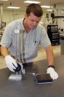 """KENNEDY SPACE CENTER, FLA. - In the Thermal Protection System Facility, Tim Wright, engineering manager with United Space Alliance, tests a new tile, called """"Boeing replacement insulation"""" or """"BRI-18."""" The new tiles will gradually replace older tiles around main landing gear doors, external tank doors and nose landing gear doors. Currently, 10 tiles have been processed inside the facility. Discovery will receive the first BRI-18 tiles. Technicians inside the Orbiter Processing Facility are performing fit checks and will begin bonding the tiles to the vehicle this month. The raw material is manufactured by The Boeing Company in Huntington Beach, Calif. Replacing older tile with the BRI-18 tile in strategic areas is one of the Columbia Accident Investigation Board's recommendations to strengthen the orbiters. The tiles are more impact resistant than previous designs, enhancing the crew?s safety."""