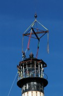 KENNEDY SPACE CENTER, FLA. - At Cape Canaveral Air Force Station, workers get ready to attach a crane to the top of the lamp room on the Cape Canaveral Lighthouse. Leaks in the roof allowed moisture to seep in. The lamp room is being removed for repairs and refurbishment. In addition, the original brass roof will be restored and put back in place. The Cape Canaveral Lighthouse is the only operational lighthouse owned by the Air Force. It was first erected in 1868 near the edge of the Atlantic Ocean. Photo credit: NASA/Jack Pfaller