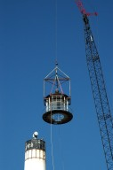 KENNEDY SPACE CENTER, FLA. - At Cape Canaveral Air Force Station, a crane swings the detached lamp room clear of the beacon on the Cape Canaveral Lighthouse. Leaks in the roof allowed moisture to seep in. The lamp room is being removed for repairs and refurbishment. In addition, the original brass roof will be restored and put back in place. The Cape Canaveral Lighthouse is the only operational lighthouse owned by the Air Force. It was first erected in 1868 near the edge of the Atlantic Ocean. Photo credit: NASA/Jack Pfaller
