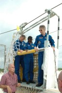 KENNEDY SPACE CENTER, FLA. - During emergency egress training at the pad, STS-121 crew members Piers Sellers, Stephanie Wilson and Thomas Reiter, all mission specialists, learn how to exit the slidewire basket on the ground. The crew is at Kennedy for Terminal Countdown Demonstration Test activities, including emergency egress training from the pad. They will also suit up in their orange flight suits for a simulated countdown to launch. Discovery is designated to launch July 1 on mission STS-121. It will carry supplies to the International Space Station. Photo credit: NASA/Kim Shiflett