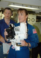 KENNEDY SPACE CENTER, FLA. - In the Orbiter Processing Facility, STS-115 Mission Specialist Heidemarie Stefanyshyn-Piper takes her turn at using a camera that is a mockup of one the crew will use to take photographs on-orbit. The crew is at the center for Crew Equipment Interface Test activities, which involves equipment familiarization, a routine part of astronaut training and launch preparations. The mission will deliver the second port truss segment, the P3/P4 Truss, to attach to the first port truss segment, the P1 Truss, as well as deploy solar array set 2A and 4A. Launch on Space Shuttle Atlantis is scheduled for late August. Photo credit: NASA/Kim Shiflett