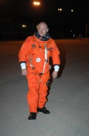 KENNEDY SPACE CENTER, FLA. - In the pre-dawn hours, STS-121 Pilot Mark Kelly heads across the Shuttle Landing Facility to the Shuttle Training Aircraft (STA). Kelly and Commander Steven Lindsey will be making practice landings in preparation for the July 1 launch of Space Shuttle Discovery. The STA is a Grumman American Aviation-built Gulf Stream II jet that was modified to simulate an orbiter?s cockpit, motion and visual cues, and handling qualities. In flight, the STA duplicates the orbiter?s atmospheric descent trajectory from approximately 35,000 feet altitude to landing on a runway. Because the orbiter is unpowered during re-entry and landing, its high-speed glide must be perfectly executed the first time. Photo credit: NASA/Kim Shiflett