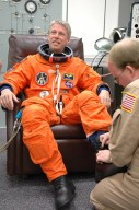 KENNEDY SPACE CENTER, FLA. - The STS-121 crew are donning their orange launch and entry suits for launch today on Space Shuttle Discovery. Having his boot worked on is Mission Specialist Thomas Reiter, who represents the European Space Agency. Reiter is making his first space shuttle flight. The launch is the 115th shuttle flight and the 18th U.S. flight to the International Space Station. During the 12-day mission, the STS-121 crew will test new equipment and procedures to improve shuttle safety, as well as deliver supplies and make repairs to the International Space Station. Photo credit: NASA/Kim Shiflett