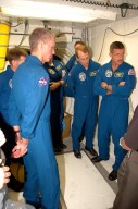 KENNEDY SPACE CENTER, FLA. - The STS-115 crew is in the White Room on the orbiter access arm on Launch Pad 39B to get instruction on using the emergency egress system. From left are Commander Brent Jett, Pilot Chris Ferguson, and Mission Specialists Heidemarie Stefanyshyn-Piper, Joseph Tanner, Steven MacLean and Daniel Burbank. MacLean is with the Canadian Space Agency. he White Room provides access into the orbiter through the crew access hatch. The mission crew is at KSC for Terminal Countdown Demonstration Test (TCDT) activities that are preparation for launch on Space Shuttle Atlantis, scheduled to take place in a window that opens Aug. 27. During their 11-day mission to the International Space Station, the STS-115 crew will continue construction of the station and attach the payload elements, the Port 3/4 truss segment with its two large solar arrays. Photo credit: NASA/Cory Huston
