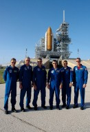 KENNEDY SPACE CENTER, FLA. - The STS-115 crew poses for the media before a press conference on Launch Pad 39B. Seen left to right are Mission Specialist Steven MacLean, Commander Brent Jett, Mission Specialist Daniel Burbank, Pilot Chris Ferguson, and Mission Specialists Heidemarie Stefanyshyn-Piper and Joseph Tanner. MacLean is with the Canadian Space Agency. The mission crew is at KSC for Terminal Countdown Demonstration Test activities that are preparation for launch on Space Shuttle Atlantis, scheduled to take place in a window that opens Aug. 27. Behind the crew is the shuttle, surrounded by the fixed and rotating service structures, with the orange external tank and while solid rocket boosters showing. The TCDT culminates in a simulated launch countdown. During their 11-day mission to the International Space Station, the STS-115 crew will continue construction of the station and attach the payload elements, the Port 3/4 truss segment with its two large solar arrays. Photo credit: NASA/Cory Huston