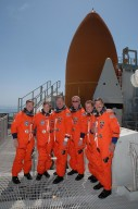 KENNEDY SPACE CENTER, FLA. - Following a simulated launch countdown and emergency egress practice, the STS-115 crew gathers on the 215-foot level of the fixed service structure on Launch Pad 39B. From left are Pilot Christopher Ferguson, Mission Specialists Heidemarie Stefanyshyn-Piper and Joseph Tanner, Commander Brent Jett, and Mission Specialists Steven MacLean and Daniel Burbank. MacLean is with the Canadian Space Agency. Behind them loom the top of Space Shuttle Atlantis' external tank and one of the solid rocket boosters. The TCDT is a prelaunch preparation for the mission that is scheduled to lift off in a window opening Aug. 27. During their 11-day mission to the International Space Station, the STS-115 crew will continue construction of the station and attach the payload elements, the Port 3/4 truss segment with its two large solar arrays. Photo credit: NASA/Cory Huston