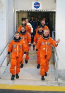 KENNEDY SPACE CENTER, FLA. - After suiting up, the STS-115 mission crew exits the Operations and Checkout Building to board the Astrovan to Launch Pad 39B. On the left, front to back, are Pilot Christopher Ferguson and Mission Specialists Steven MacLean and Heidemarie Stefanyshyn-Piper. On the right, front to back, are Commander Brent Jett and Mission Specialists Daniel Burbank and Joseph Tanner. The launch attempt on Sept. 8 was scrubbed due to an issue with a fuel cut-off sensor system inside the external fuel tank. This is one of several systems that protect the shuttle's main engines by triggering their shutdown if fuel runs unexpectedly low. During the STS-115 mission, Atlantis' astronauts will deliver and install the 17.5-ton, bus-sized P3/P4 integrated truss segment on the station. The girder-like truss includes a set of giant solar arrays, batteries and associated electronics and will provide one-fourth of the total power-generation capability for the completed station. This mission is the 116th space shuttle flight, the 27th flight for orbiter Atlantis, and the 19th U.S. flight to the ISS. STS-115 is scheduled to last 11 days with a planned landing at KSC. Photo credit: NASA/Kim Shiflett