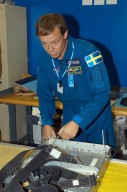 KENNEDY SPACE CENTER, FLA. - At SPACEHAB in Cape Canaveral, Fla., STS-116 Mission Specialist Christer Fuglesang practices techniques for removing and replacing the rack front stowage tray, used inside the SPACEHAB module. Fuglesang , from Sweden, represents the European Space Agency. Mission crews make frequent trips to the Space Coast to become familiar with the equipment and payloads they will be using. STS-116 will be mission number 20 to the International Space Station and construction flight 12A.1. The mission payload is the SPACEHAB module, the P5 integrated truss structure and other key components. Launch is scheduled for no earlier than Dec. 7. Photo credit: NASA/George Shelton