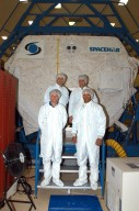 """KENNEDY SPACE CENTER, FLA. - At SPACEHAB in Cape Canaveral, Fla., STS-116 crew members are dressed in """"bunny suits"""" before going inside the SPACEHAB module. In front are Mission Specialists Christer Fuglesang and Robert Curbeam; in back are Commander Mark Polansky and Pilot William Oefelein. Fuglesang, from Sweden, represents the European Space Agency. Mission crews make frequent trips to the Space Coast to become familiar with the equipment and payloads they will be using. STS-116 will be mission number 20 to the International Space Station and construction flight 12A.1. The mission payload is the SPACEHAB module, the P5 integrated truss structure and other key components. Launch is scheduled for no earlier than Dec. 7. Photo credit: NASA/George Shelton"""