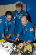 KENNEDY SPACE CENTER, FLA. - At SPACEHAB in Cape Canaveral, Fla., STS-116 Pilot William Oefelein, Mission Specialist Christer Fuglesang and Commander Mark Polansky check data on a computer while examining the rack front stowage trays that are used inside the SPACEHAB module. Mission crews make frequent trips to the Space Coast to become familiar with the equipment and payloads they will be using. STS-116 will be mission number 20 to the International Space Station and construction flight 12A.1. The mission payload is the SPACEHAB module, the P5 integrated truss structure and other key components. Launch is scheduled for no earlier than Dec. 7. Photo credit: NASA/George Shelton