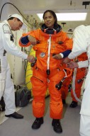 KENNEDY SPACE CENTER, FLA. -- In the white room on Launch Pad 39B, STS-116 Mission Specialist Joan Higginbotham is helped with her gear before entering Space Shuttle Discovery. The mission crew is taking part in a simulated launch countdown, part of the terminal countdown demonstration test that includes prelaunch preparations. The STS-116 mission is No. 20 to the International Space Station and construction flight 12A.1. The mission payload is the SPACEHAB module, the P5 integrated truss structure and other key components. Launch is scheduled for no earlier than Dec. 7. Photo credit: NASA/Amanda Diller
