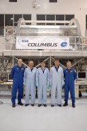 KENNEDY SPACE CENTER, FLA. -- In the Space Station Processing Facility, STS-122 crew members pause for a photo in front of the Columbus European Laboratory, part of the payload on their mission. From left are Pilot Alan Poindexter, Mission Specialists Hans Schlegel, Rex Walheim and Stan Love, and Commander Steve Frick. Schlegel represents the European Space Agency. The crew is participating in a crew equipment interface test that provides opportunities for hands-on experience with payloads and equipment. The 24th mission to the International Space Station, STS-122 will also include the Multi-Purpose Experiment Support Structure - Non-Deployable (MPESS-ND). Launch of STS-122 on Space Shuttle Discovery is scheduled no earlier than October. Photo credit: NASA/Kim Shiflett