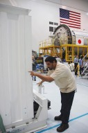 """KENNEDY SPACE CENTER, FLA. -- On the floor of the Space Station Processing Facility, a worker checks the placement of the container with the Japanese Experiment Module (JEM) remote manipulator system inside. The Japanese Aerospace Exploration Agency developed the laboratory known as """"Kibo"""" (Hope) and includes an exposed facility (platform) for space environment experiments, the RMS and two logistics modules. Japan's primary contribution to the International Space Station, it will enhance the unique research capabilities of the orbiting complex by providing an additional environment for astronauts to conduct science experiments. The various JEM components will be assembled in space over the course of three Shuttle missions. The JEM and RMS are scheduled to launch on mission STS-124 no earlier than February 2008. Photo credit: NASA/Dimitri Gerondidakis"""