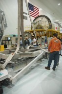 """KENNEDY SPACE CENTER, FLA. -- Using an overhead crane, workers move the ground support equipment that will be used to lift the Japanese Experiment Module (JEM) remote manipulator system after it is uncrated. The Japanese Aerospace Exploration Agency developed the laboratory known as """"Kibo"""" (Hope) and includes an exposed facility (platform) for space environment experiments, the RMS and two logistics modules. Japan's primary contribution to the International Space Station, it will enhance the unique research capabilities of the orbiting complex by providing an additional environment for astronauts to conduct science experiments. The various JEM components will be assembled in space over the course of three Shuttle missions. The JEM and RMS are scheduled to launch on mission STS-124 no earlier than February 2008. Photo credit: NASA/Dimitri Gerondidakis"""