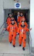 KENNEDY SPACE CENTER, FLA. -- Dressed in their flights suits, the Mission STS-117 crew members practice walk out from the Operations and Checkout Building to the astronaut van for transport to Launch Pad 39A during terminal countdown demonstration test activities. At left from the front are Pilot Lee Archambault and Mission Specialists Steven Swanson and Danny Olivas. At right from the front are Commander Rick Sturckow and Mission Specialists Patrick Forrester and James Reilly. The STS-117 mission is No. 21 to the International Space Station. Mission payloads aboard Atlantis include the S3/S4 integrated truss structure, a third set of solar arrays and batteries. The crew of six astronauts will install the truss to continue assembly of the station. Launch is scheduled for no earlier than March 15. Photo credit: NASA/Kim Shiflett.