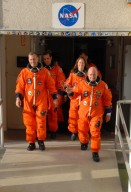 KENNEDY SPACE CENTER, Fla. -- The STS-118 crew walks out of the Operations and Checkout Building, heading for Launch Pad 39A and a simulated launch countdown. On the left, Pilot Charlie Hobaugh leads one column, with Mission Specialist Rick Mastracchio behind him. On the right, Commander Scott Kelly leads, with Mission Specialists Tracy Caldwell and Dave Williams behind. Not pictured are Mission Specialists Alvin Drew and teacher-turned-astronaut Barbara R. Morgan. The countdown concludes the terminal countdown demonstration test, or TCDT. The STS-118 crew has been at Kennedy for the TCDT activities that also include M-113 training, payload familiarization and emergency egress training at the pad. The mission is the 22nd flight to the International Space Station and Space Shuttle Endeavour will carry a payload including the S5 truss, a SPACEHAB module and external stowage platform 3. STS-118 is targeted for launch on Aug. 7. Photo credit: NASA/George Shelton