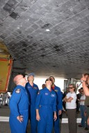 KENNEDY SPACE CENTER, FLA. -- Members of the STS-118 crew take a close look at the damaged tile on the underside of Endeavour. From left are Commander Scott Kelly and Mission Specialists Dave Williams, Tracy Caldwell and Rick Mastracchio On the mission, the crew installed a new gyroscope, an external spare parts platform and another truss segment to the expanding station. Endeavour's main gear touched down at 12:32:16 p.m. EDT. Nose gear touchdown was at 12:32:29 p.m. and wheel stop was at 12:33:20 p.m. Endeavour landed on orbit 201. STS-118 was the 119th space shuttle flight, the 22nd flight to the station, the 20th flight for Endeavour and the second of four missions planned for 2007. This was the 65th landing of an orbiter at Kennedy. Photo credit: NASA/Kim Shiflett