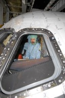 KENNEDY SPACE CENTER, FLA. -- In the Orbiter Processing Facility, STS-122 Commander Stephen Frick checks out the cockpit on space shuttle Atlantis. He and other crew members are at Kennedy Space Center to take part in a crew equipment interface test, which helps familiarize them with equipment and payloads for the mission. Among the activities standard to a CEIT are harness training, inspection of the thermal protection system and camera operation for planned extravehicular activities, or EVAs. The mission will carry and install the Columbus Lab, a multifunctional, pressurized laboratory that will be permanently attached to Node 2 of the space station to carry out experiments in materials science, fluid physics and biosciences, as well as to perform a number of technological applications. It is Europe?s largest contribution to the construction of the International Space Station and will support scientific and technological research in a microgravity environment. STS-122 is targeted for launch in December. Photo credit: NASA/Kim Shiflett